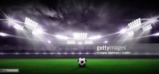 soccer ball on land against sky at night - stadium stock pictures, royalty-free photos & images