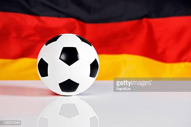 Fußball ball auf reflektierende Oberfläche mit Deutschland-Flagge