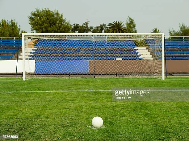 A soccer ball on the penalty marker in front of a goal