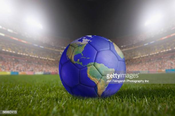 soccer ball painted like a globe resting on grass in large stadium - world sports championship photos et images de collection