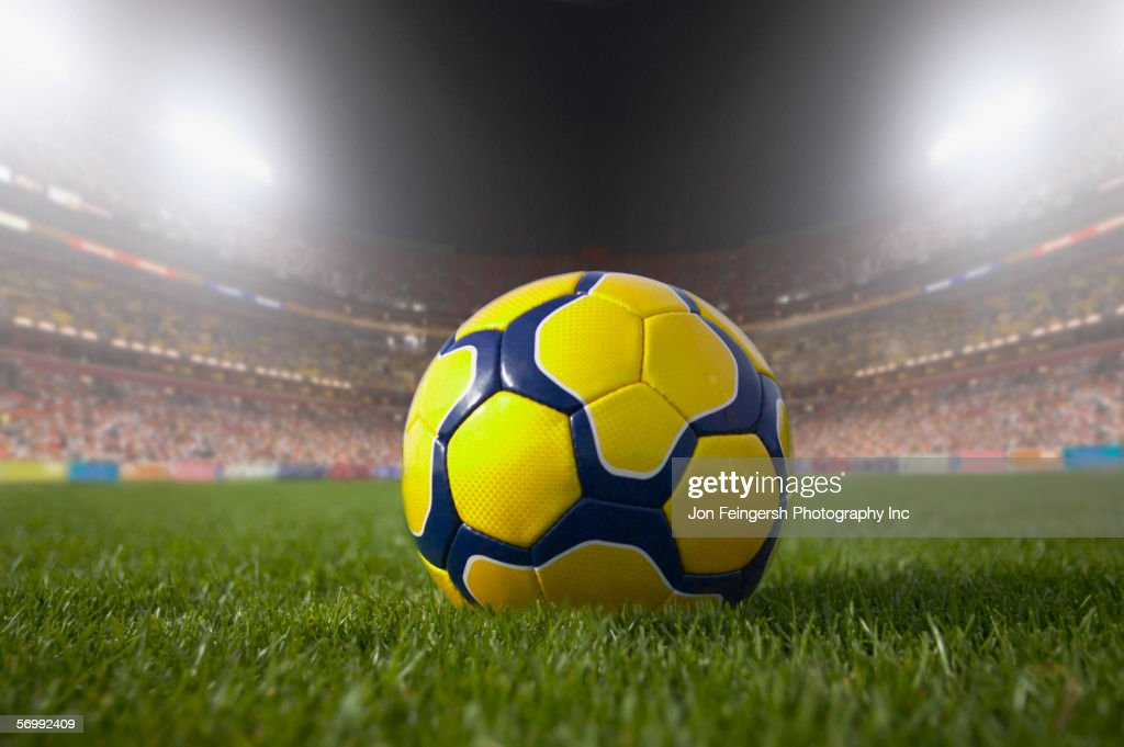 Soccer ball resting on grass in large stadium : Stock Photo