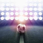 Soccer ball rolling towards stadium lights