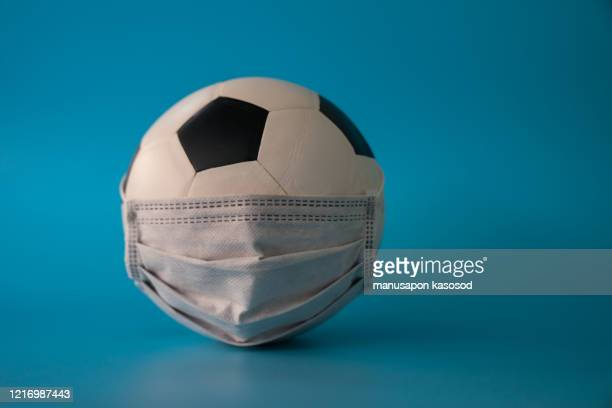 soccer ball with protective mask - virus - football face mask stock pictures, royalty-free photos & images
