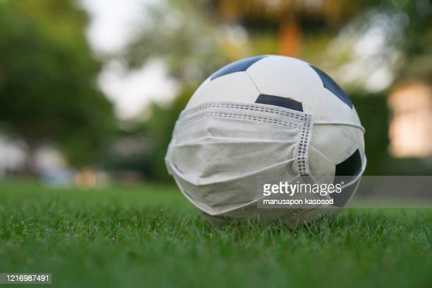 soccer ball with protective mask - virus - sport stock pictures, royalty-free photos & images