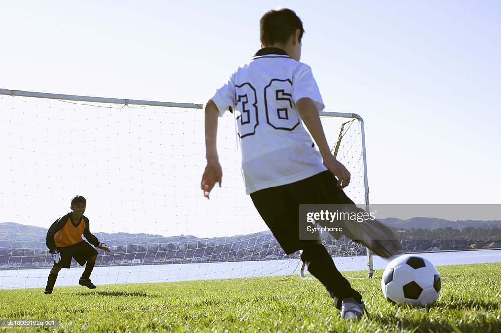 Soccer boy taking shot at goal, goalkeeper watching : Stockfoto