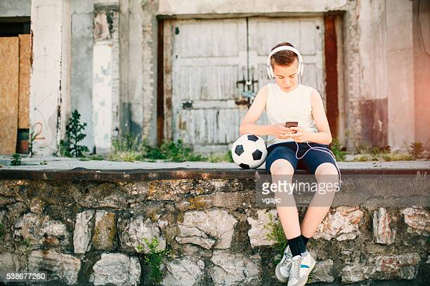 Soccer Boy Using His Smart Phone Outdoors.