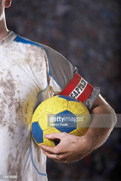 soccer captain holding ball underarm, close up of ball - captain's armband stock photos and pictures