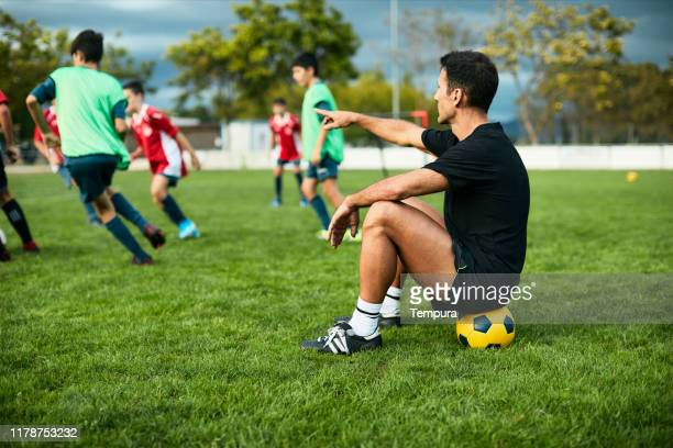 soccer coach directing a training session in the field. - calcio di squadra foto e immagini stock