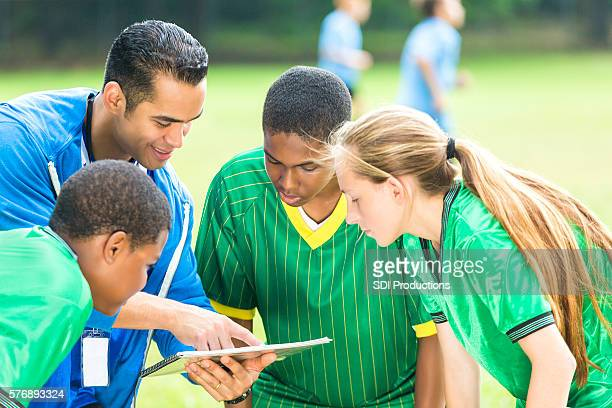 Soccer coach discusses play with team during halftime