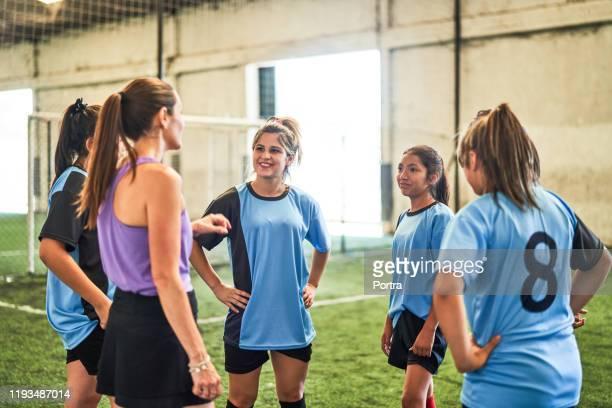 entraîneur de football expliquant la stratégie de jeu à l'équipe - tenue de football photos et images de collection