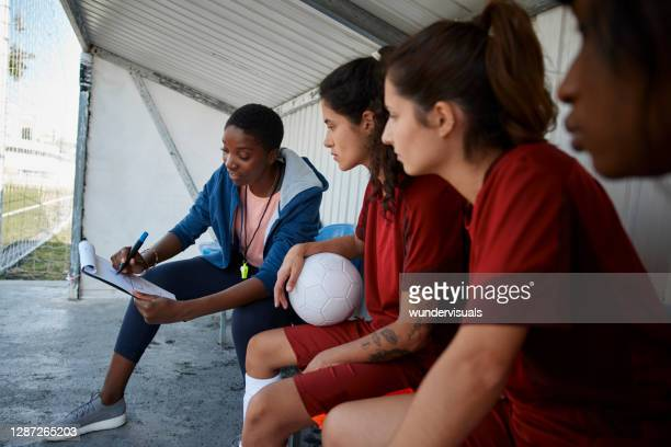 soccer coach explaining match strategies to her female soccer team - coach stock pictures, royalty-free photos & images