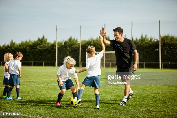 entrenador de fútbol con un chico durante la práctica - entrenador fotografías e imágenes de stock