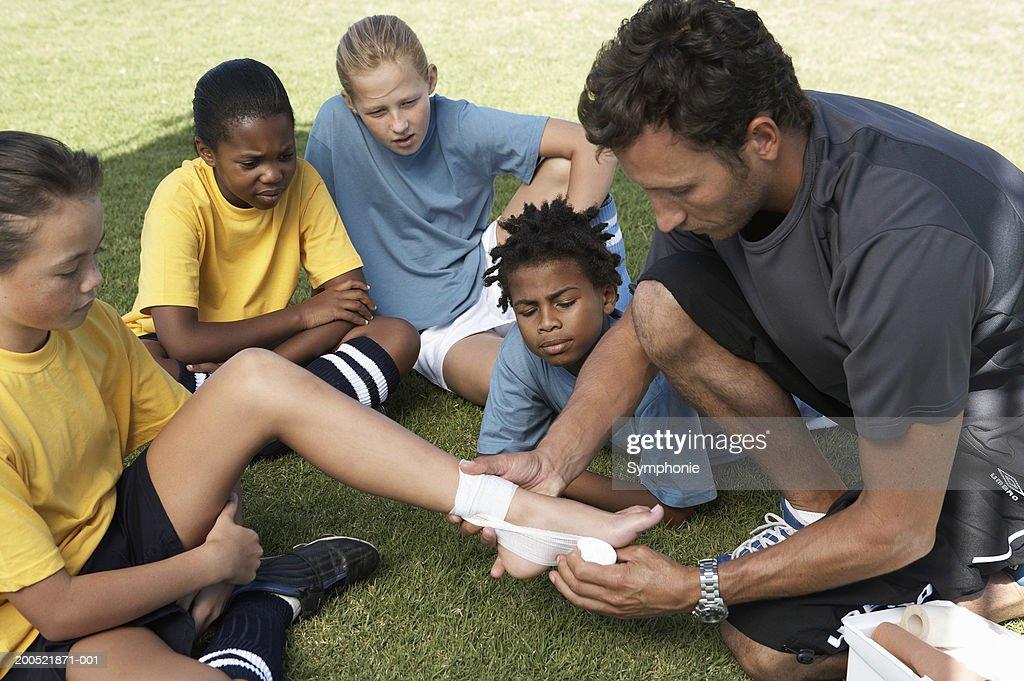 Soccer coach showing children (9-12) first aid : Foto de stock