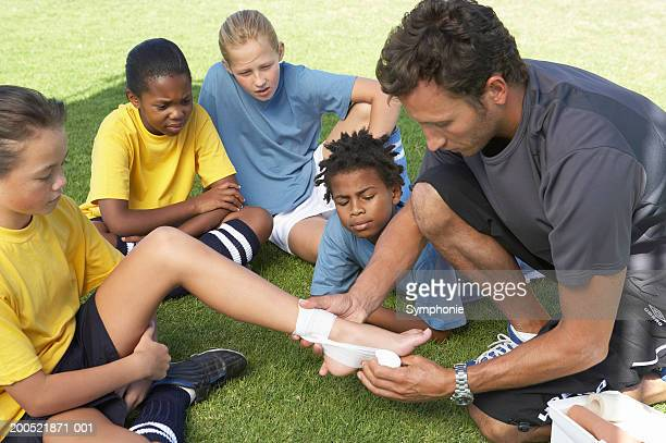 soccer coach showing children (9-12) first aid - kids first aid kit stock pictures, royalty-free photos & images