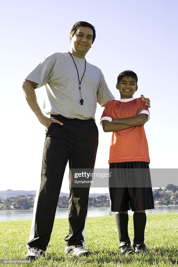 Soccer coach standing with boy, smiling, portrait : Stockfoto