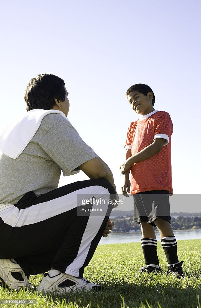 Soccer coach talking to boy, side view : Stockfoto