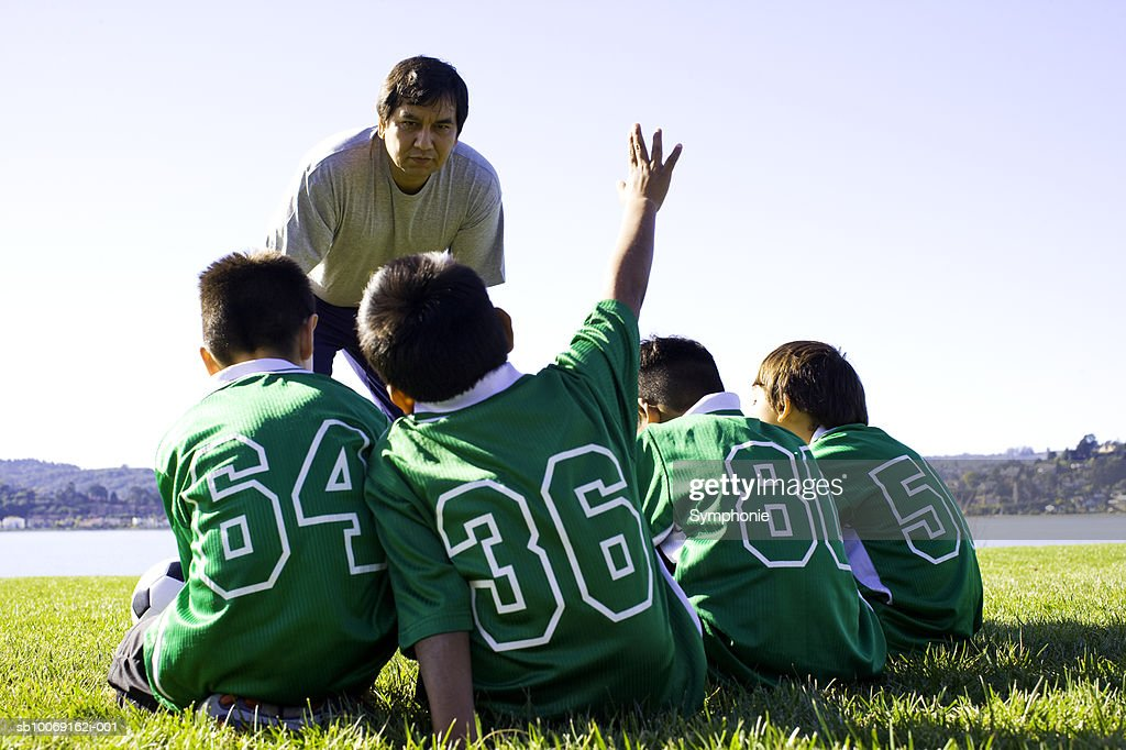 soccer coach talking to boys : Stockfoto