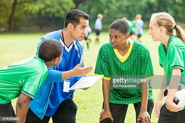 soccer coach talks about play during time out - high school football stock pictures, royalty-free photos & images