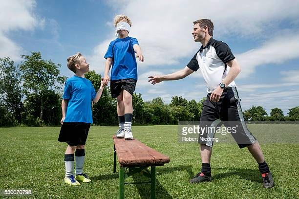 Soccer coach teaching young player trust