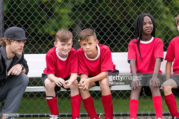 Soccer coach with his diverse childrens soccer team