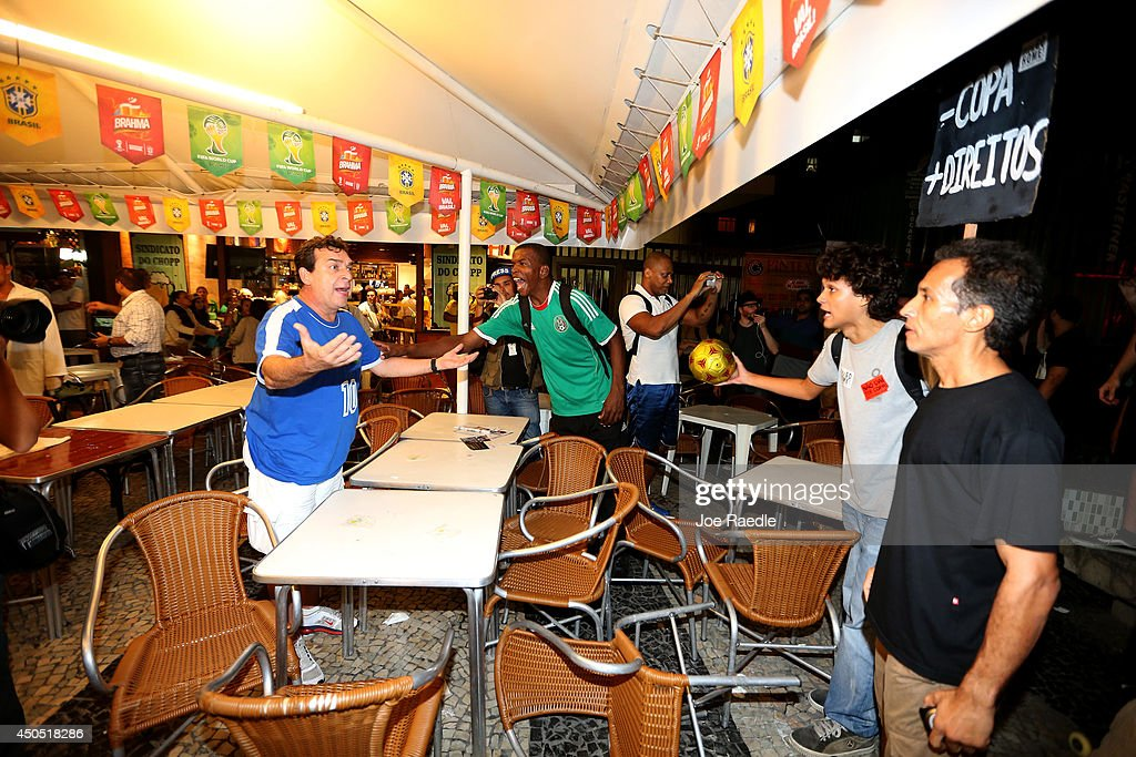 A soccer fan (L) and an anti-World Cup protester yell at each other at a restaurant that was showing the game on Copacabana beach on June 12, 2014 in Rio de Janeiro, Brazil. Brazil defeated Croatia 3-1 in the first match of 2014 FIFA World Cup today.