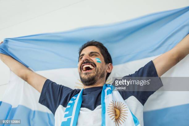 Soccer fan cheering for national team at the game