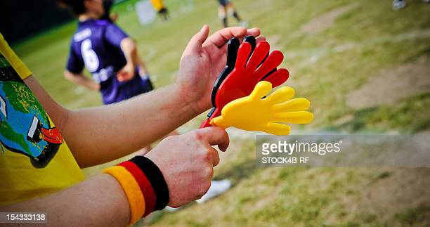 Soccer fan clapping hands at soccer pitch