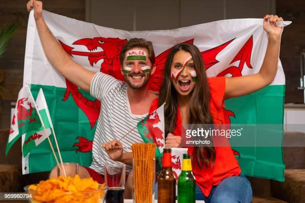 pareja de ventilador de fútbol animando a país de gales - gales fotografías e imágenes de stock