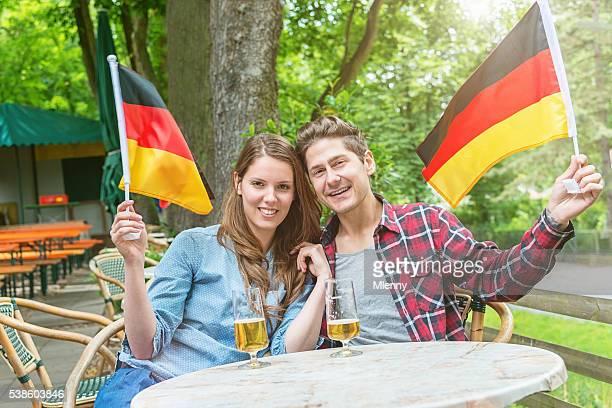 Ventilador de fútbol pareja en jardín de cerveza con bandera alemana