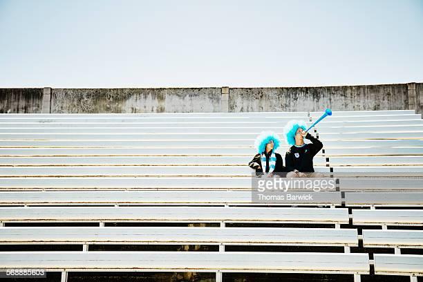 Soccer fan couple sitting in empty stadium