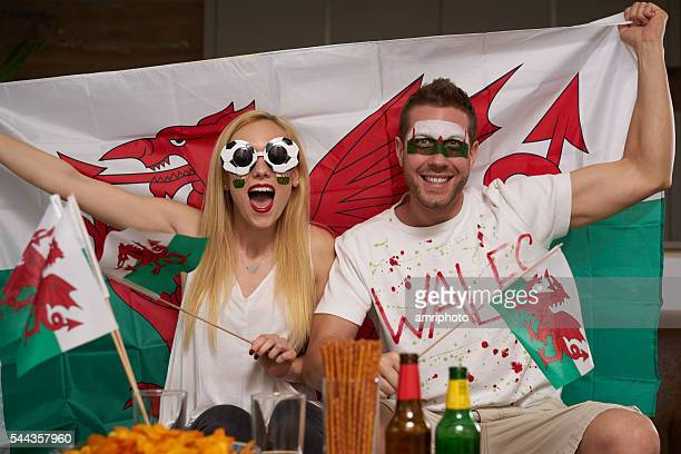 soccer fan couple supporting wales - welsh flag stock pictures, royalty-free photos & images
