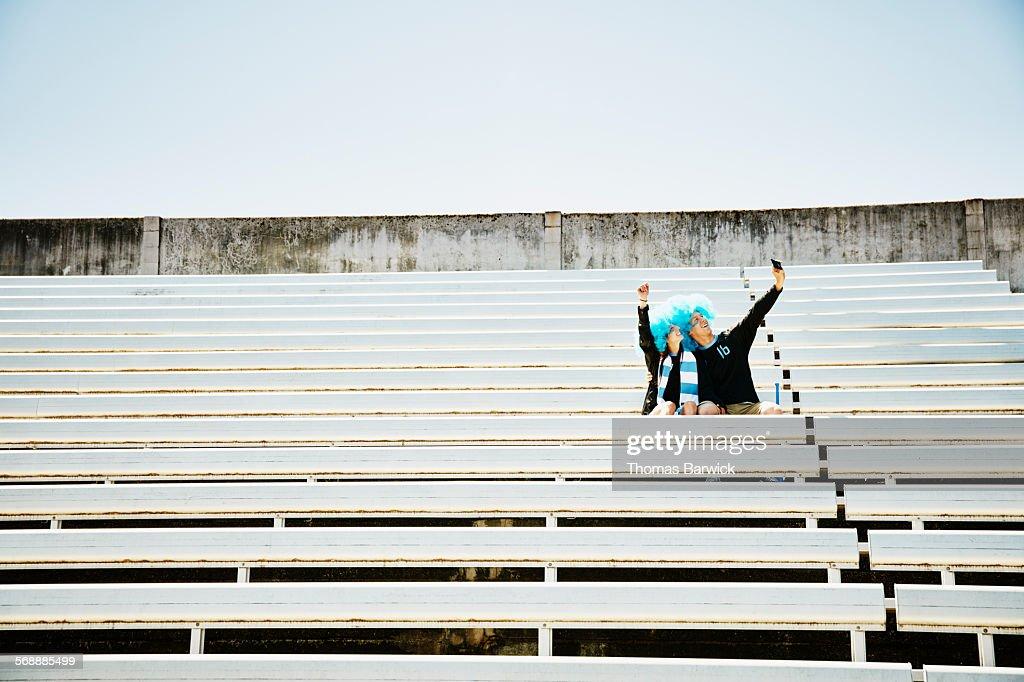 Soccer fan couple taking selfie in empty stadium : Stock Photo