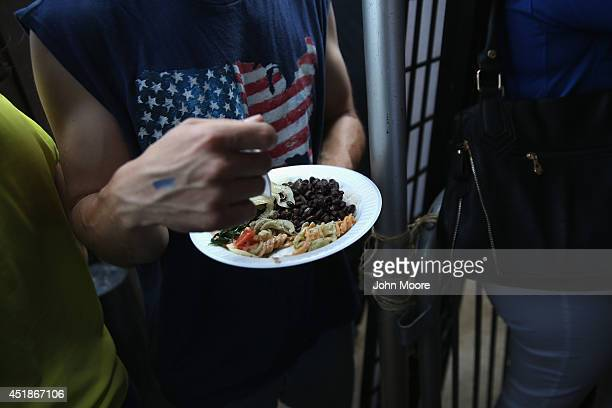 A soccer fan eats from a plate of traditional Brazilian feijoada during the semifinal World Cup game against Germany on July 8 2014 in Port Chester...
