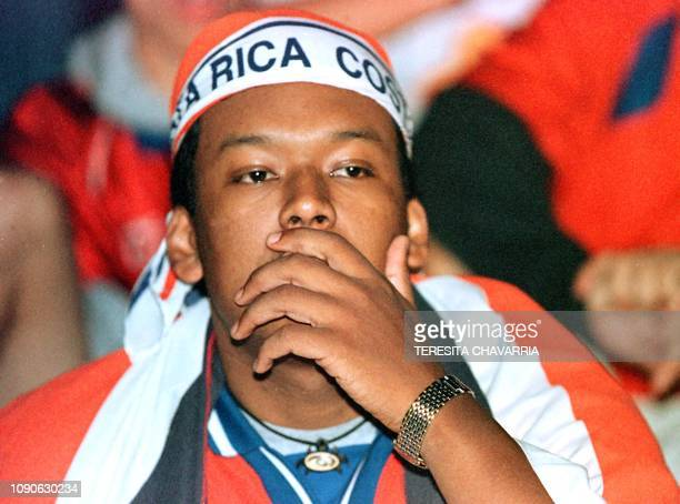 A soccer fan in Costa Rica worries as he watches his team play against Brazil at the World Cup Soccer Championship over a large screen television in...