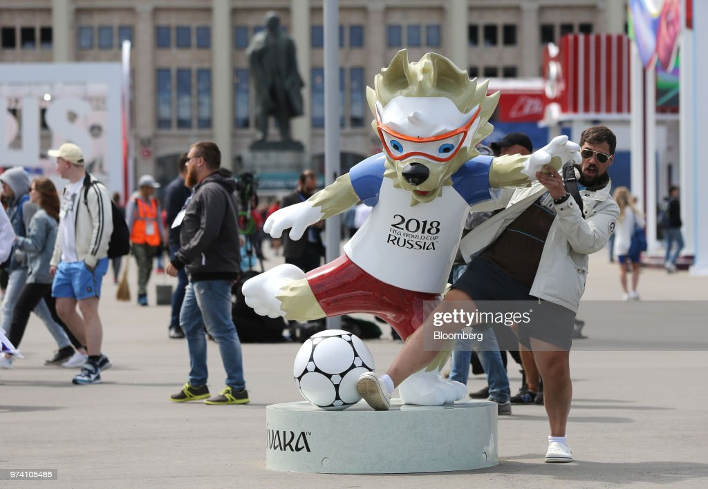 A soccer fan poses beside the Zabivaka mascot for the FIFA World Cup outside the Luzhniki stadium in Moscow, Russia, on Thursday, June 14, 2018. President Vladimir Putin has spent six years and more than $11 billion preparing nearly a dozen Russian cities to host the soccer World Cup, the biggest such event the countrys held since the collapse of the Soviet Union. Photographer: Andrey Rudakov/Bloomberg via Getty Images