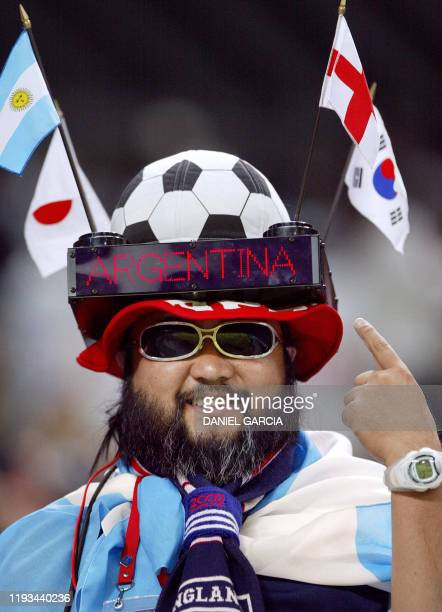 A soccer fan wearing a hat with the Argentinian Japanese Korean and English flags waits for the Group F first round match Argentina/England of the...