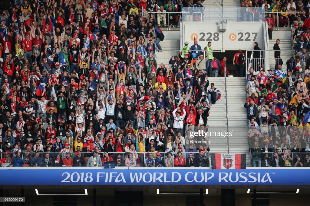 Soccer fans celebrate during the opening match of the FIFA World Cup between Russia and Saudi Arabia at the Luzhniki stadium in Moscow, Russia, on Thursday, June 14, 2018. President Vladimir Putin has spent six years and more than $11 billion preparing nearly a dozen Russian cities to host the soccer World Cup, the biggest such event the countrys held since the collapse of the Soviet Union. Photographer: Andrey Rudakov/Bloomberg via Getty Images
