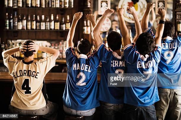 soccer fans cheering in bar - rivaliteit stockfoto's en -beelden