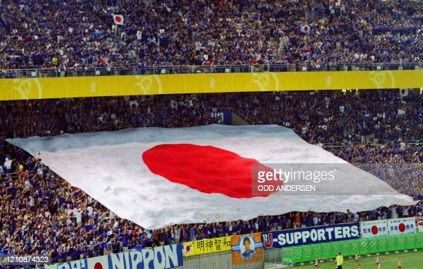 Soccer fans deploy a Japanese flag before the Group H first round match Japon/Russia of the 2002 FIFA World Cup in Korea and Japan 09 June 2002 at...