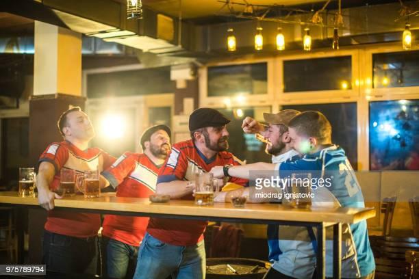 fãs de futebol que luta no bar - taking a shot sport - fotografias e filmes do acervo