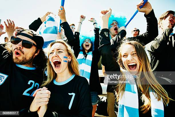 Soccer fans in stadium celebrating team victory