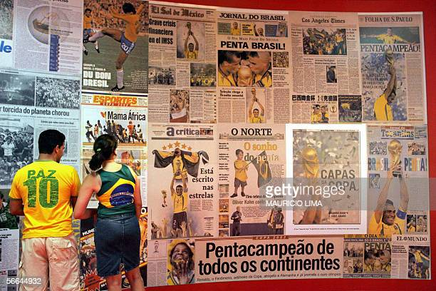 Soccer fans look at dozens of worldwide newspapers publishing pictures of the Brazilian victory in the 2002 JapanKorea World Cup in the exhibition of...