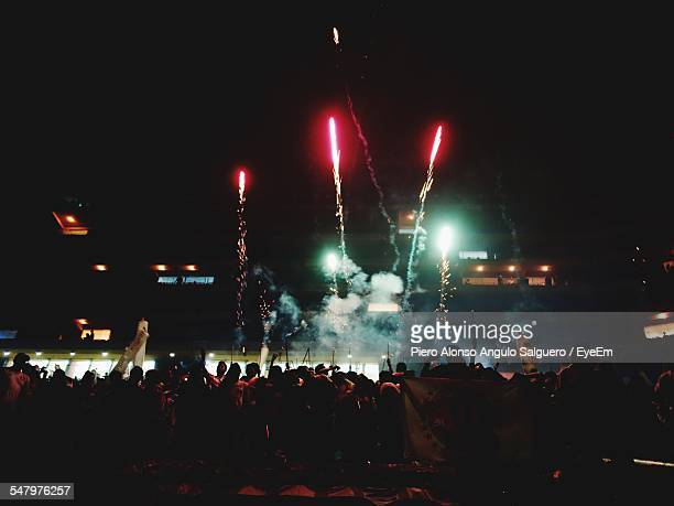 soccer fans watching fireworks display at night - flare stack stock photos and pictures