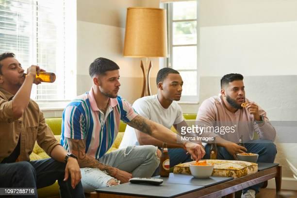 soccer fans watching match on tv at home - taking a shot sport - fotografias e filmes do acervo