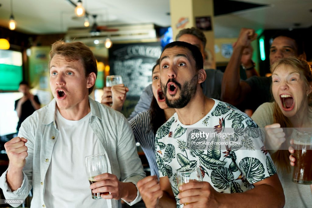 Soccer fans watching match together at pub : Stock Photo