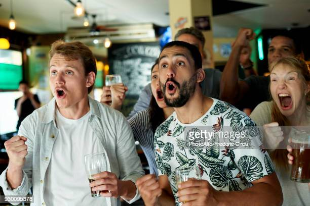 soccer fans watching match together at pub - cheering stock pictures, royalty-free photos & images