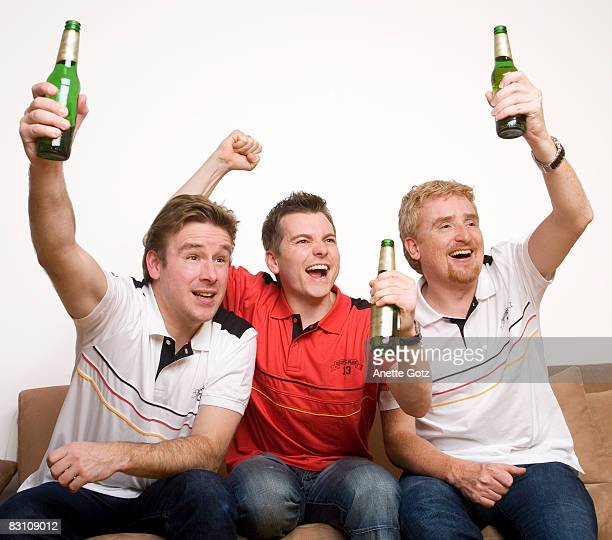 Three friends watching TV, cheering with beer bottle