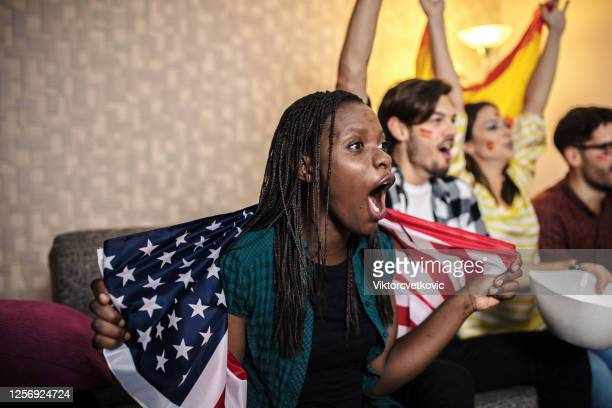 soccer fans watching the game at home on television - fan enthusiast stock pictures, royalty-free photos & images