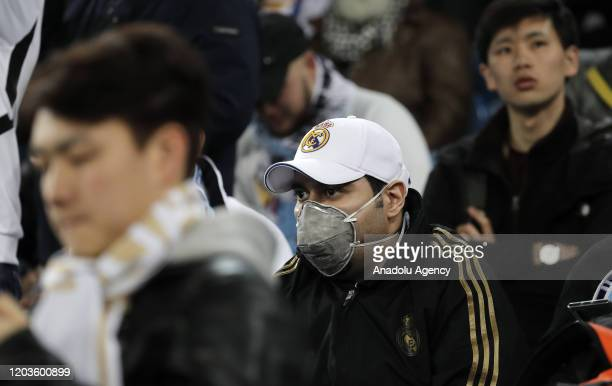 Soccer fans wear masks to protect themselves from coronavirus during the UEFA Champions League round of 16 first leg soccer match between Real Madrid...