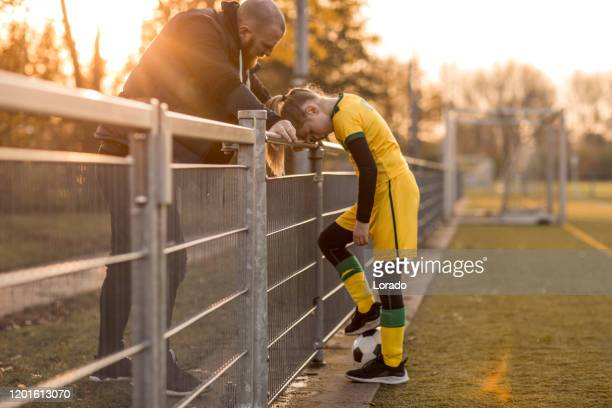 soccer father coaching football daughter during a game - sideline stock pictures, royalty-free photos & images